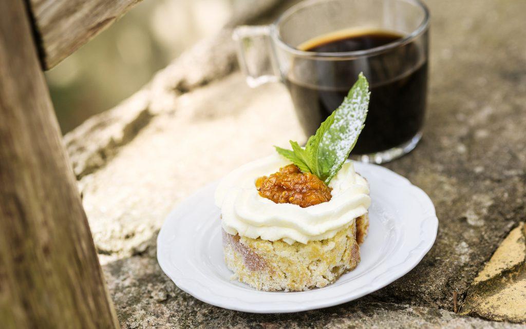 En bakelse på en tallrik vid sidan av en kopp kaffe